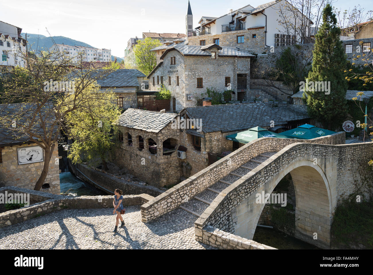 A young woman walks near an old bridge on April 15, 2015 in Mostar, Bosnia and Herzegovina. - Stock Image