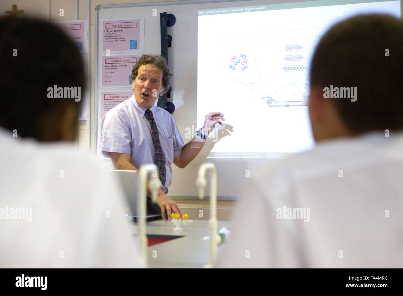 Secondary School teacher using the whiteboard to explain the background to car combustion and air quality - Stock Image