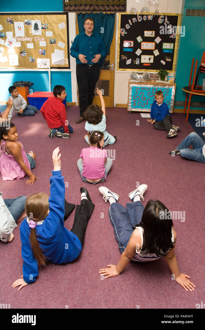 Teacher standing at front of classroom talking to group of school children, - Stock Image