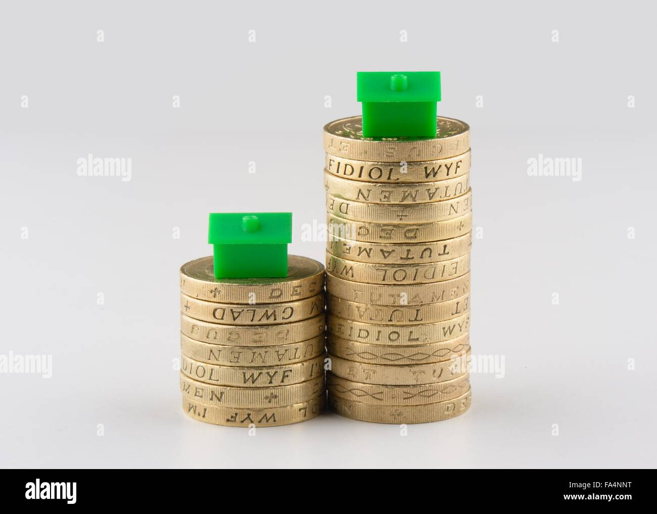 Two piles of UK pound coins with plastic houses on top suggestive of downsizing or the housing market. - Stock Image