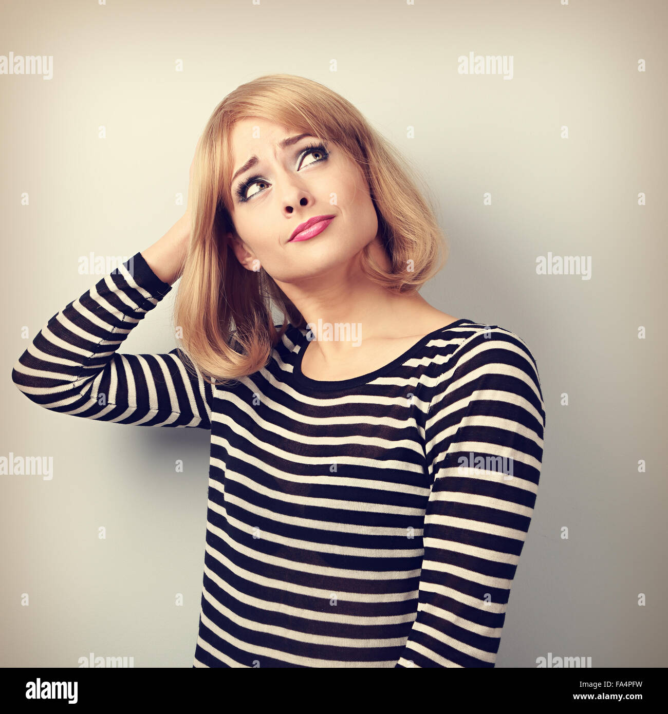 Disappointed young casual blond woman scratching the head and looking up on empty copy space background. Toned portrait - Stock Image