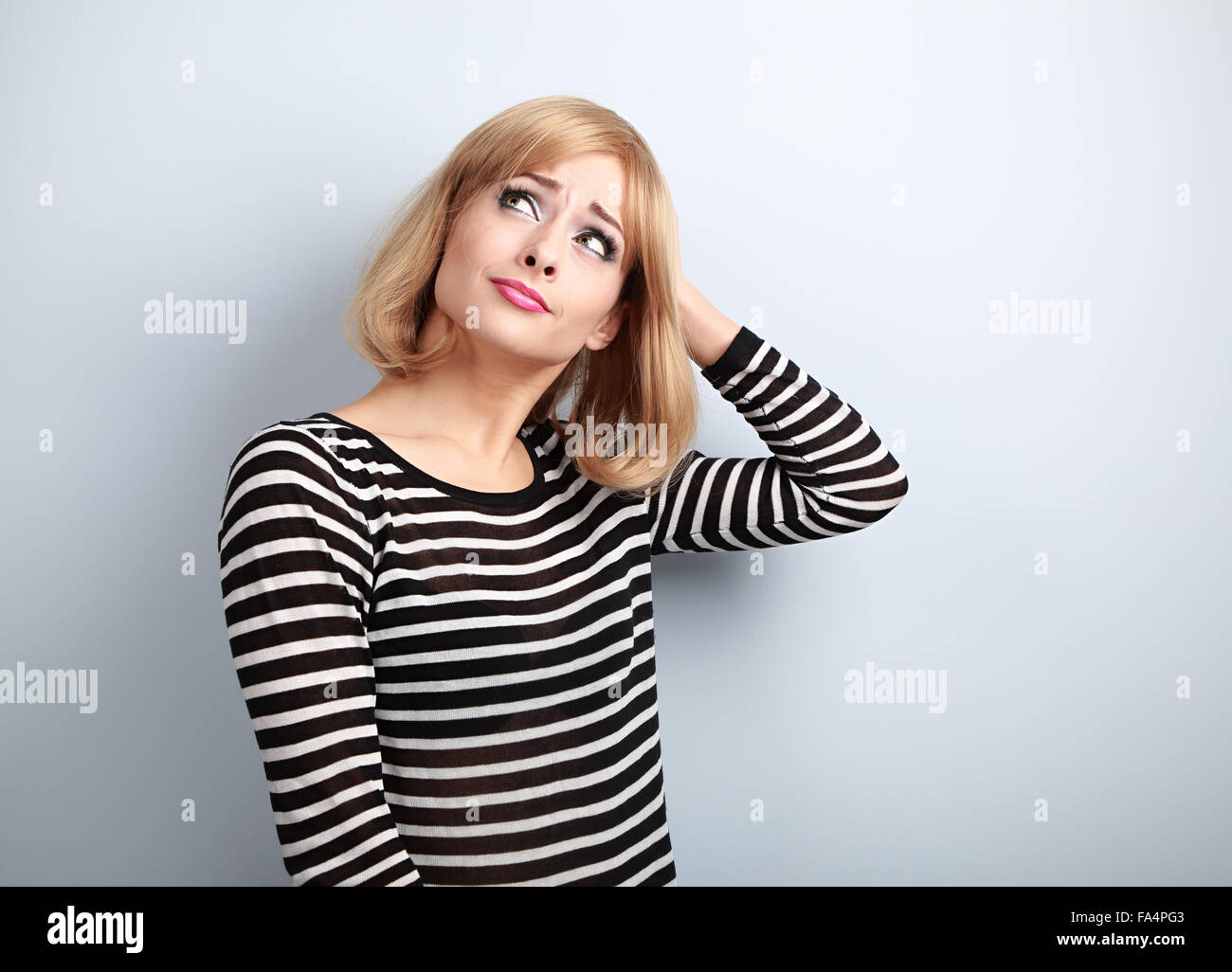 Disappointed young casual blond woman scratching the head and looking up on empty copy space blue background - Stock Image