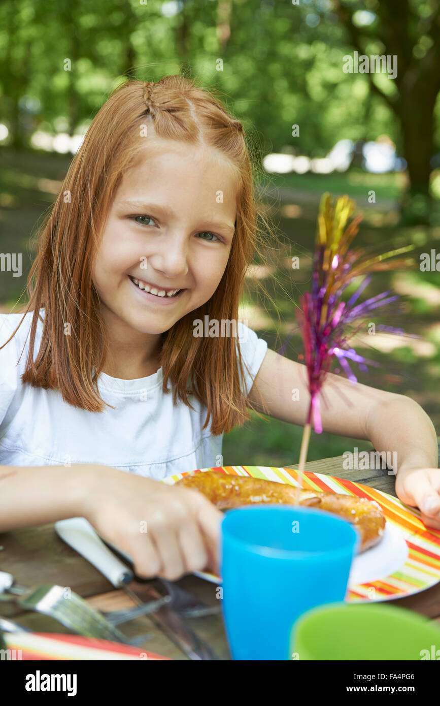 Portrait of a girl eating food at picnic, Munich, Bavaria, Germany - Stock Image