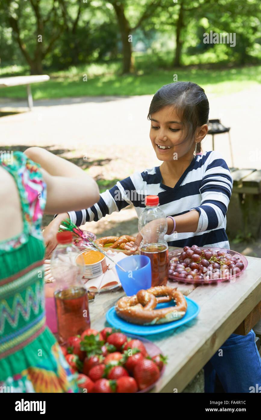 Girl eating food and smiling at picnic, Munich, Bavaria, Germany - Stock Image