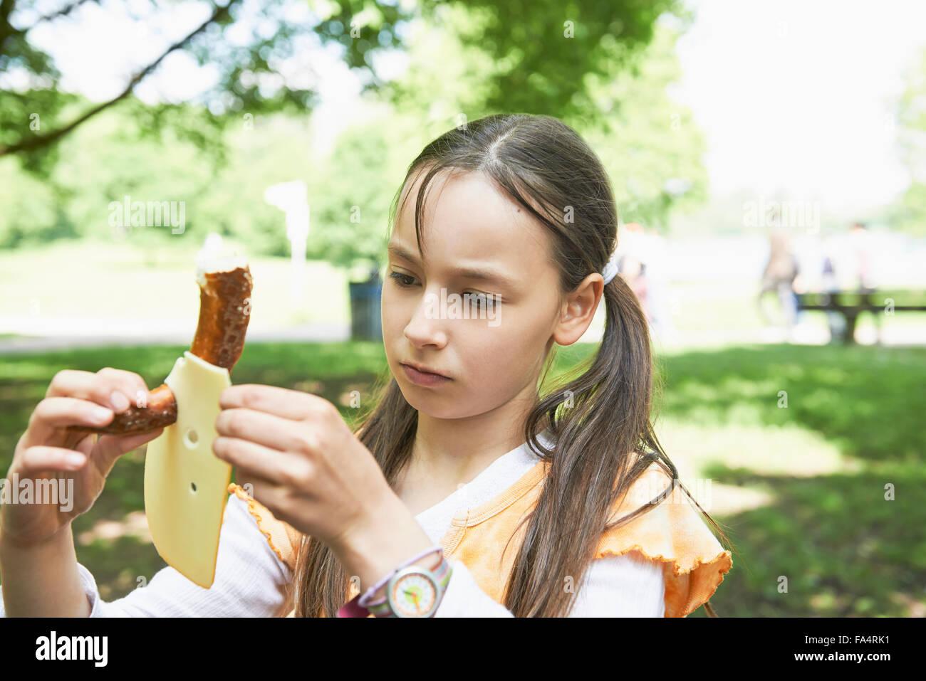 Girl inserting sausage into cheese, Munich, Bavaria, Germany - Stock Image