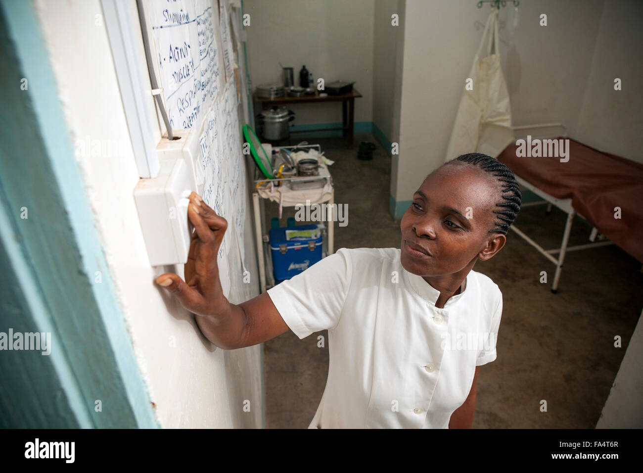 A nurse switches on a light switch at a solar-powered health centre in Bitale village, Kigoma Region, Western Tanzania. - Stock Image