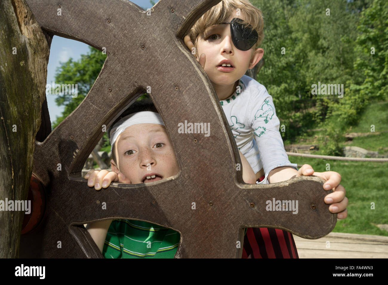 Two boys peeking from rudder of a pirate ship in adventure playground, Bavaria, Germany - Stock Image