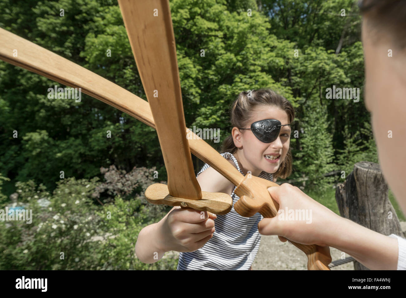 Two girls pretending as pirates fighting with swords in adventure playground, Bavaria, Germany - Stock Image
