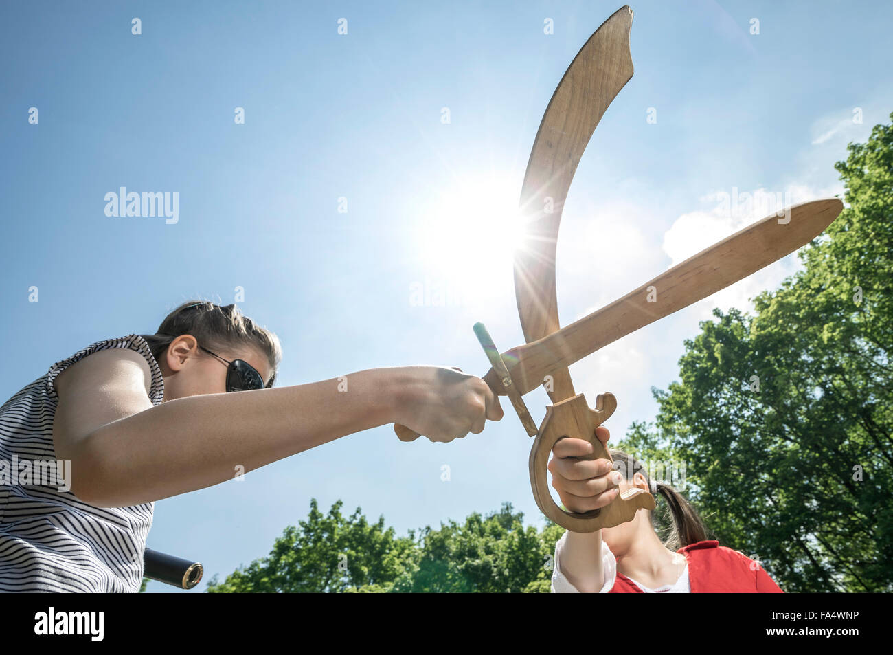 Low angle view of two girls pretending as pirates fighting with swords in adventure playground, Bavaria, Germany - Stock Image