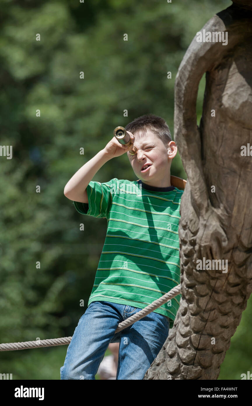 Boy standing on a ship and looking through a telescope in adventure playground, Bavaria, Germany - Stock Image