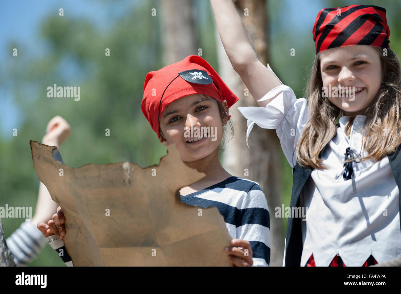 Portrait of girls holding treasure map in adventure playground, Bavaria, Germany - Stock Image