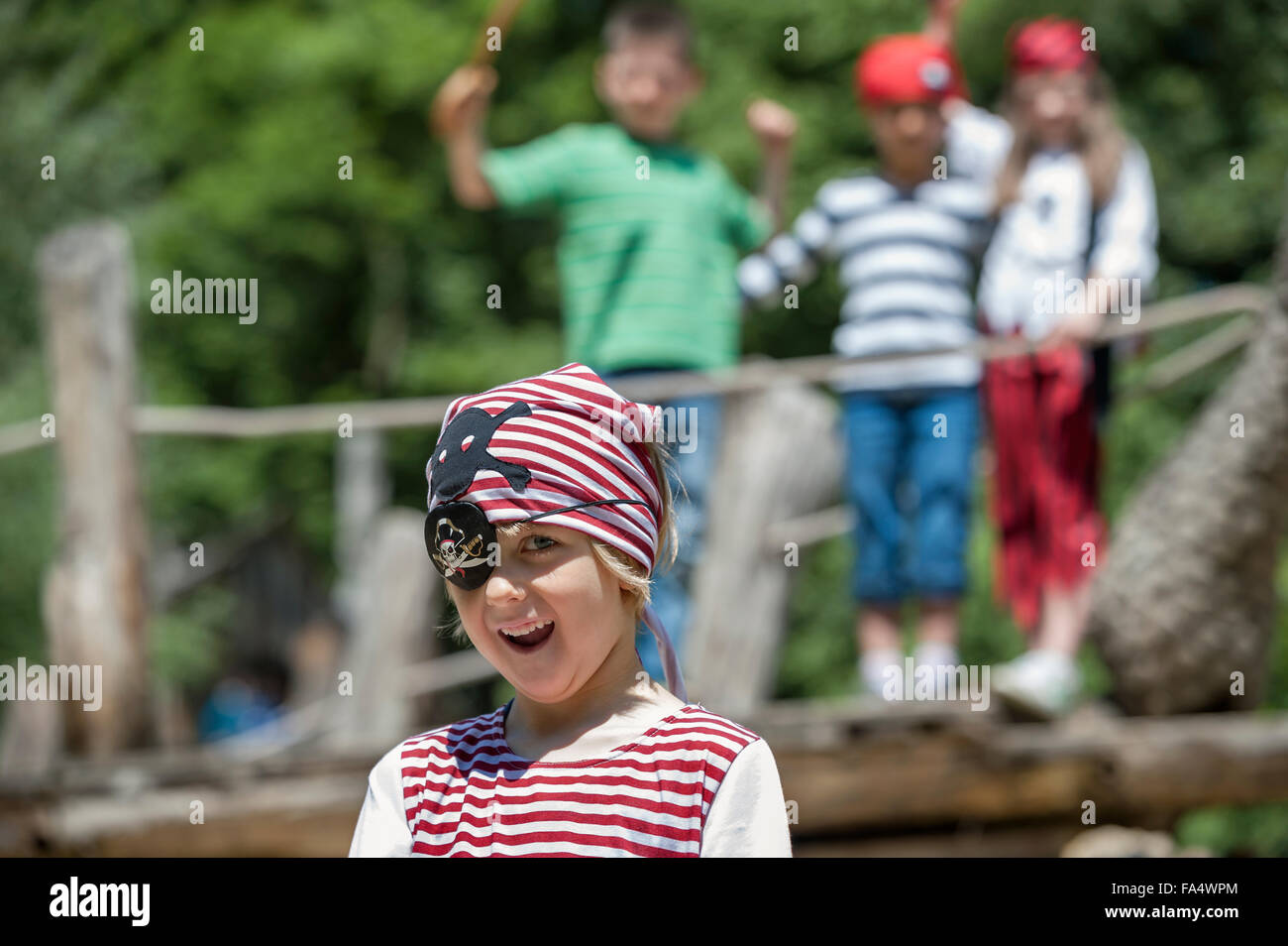 Boy dressed up as a pirate playing in adventure playground with his friends in the background, Bavaria, Germany Stock Photo