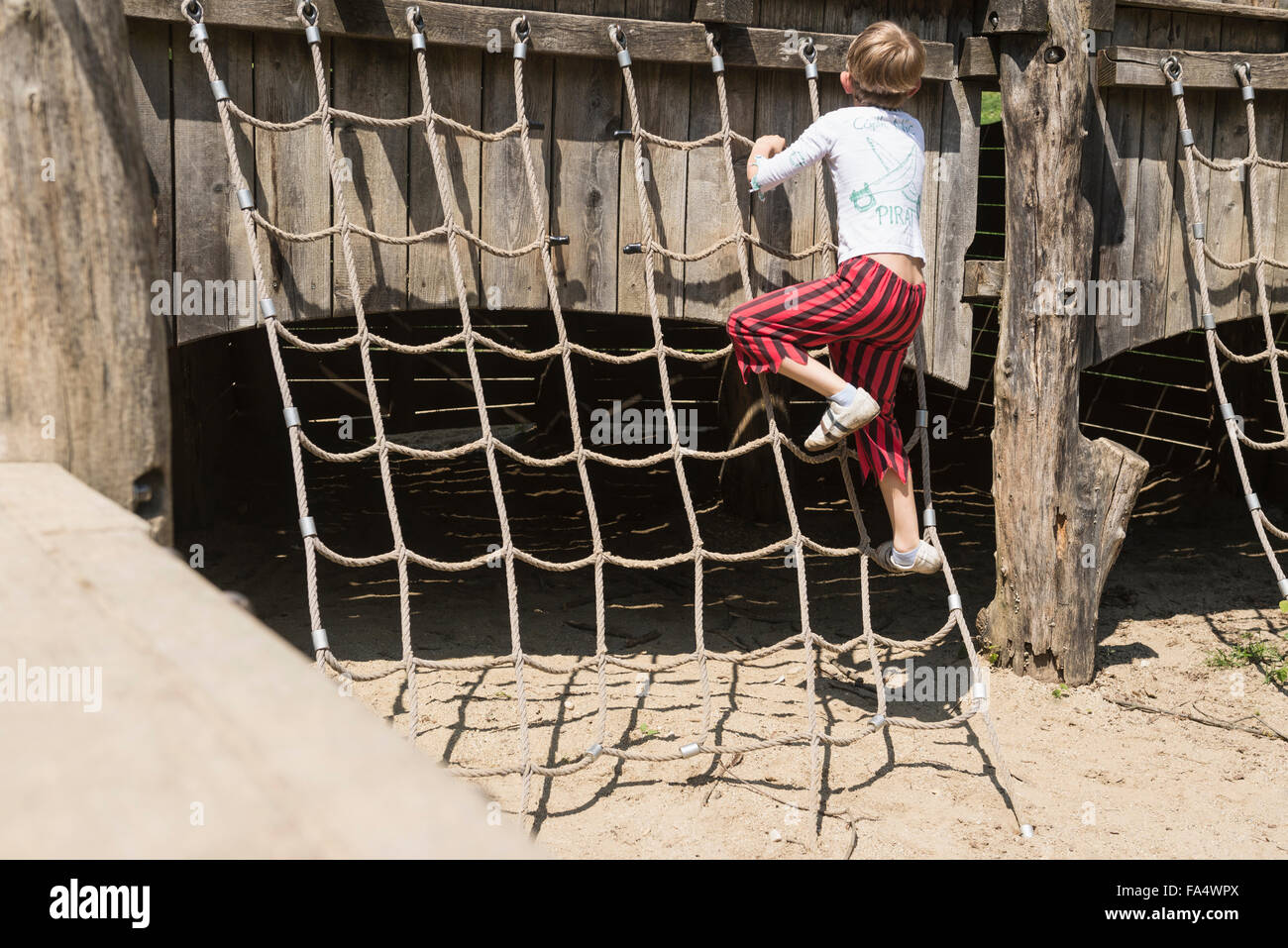 Rear view of a boy climbing on rope in adventure playground, Bavaria, Germany - Stock Image
