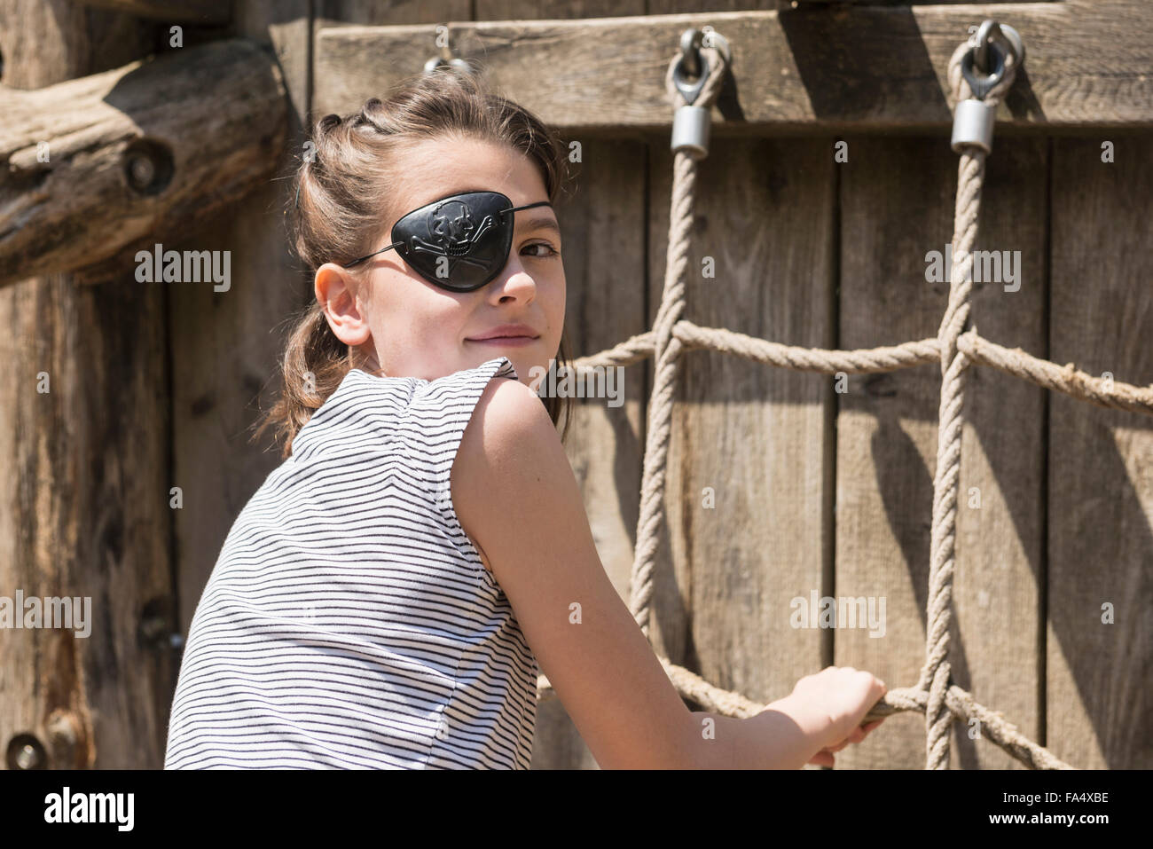Portrait of a girl climbing on rope in adventure playground, Bavaria, Germany Stock Photo