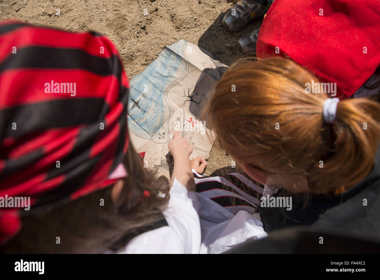 Girls examining a treasure map in a adventure playground, Bavaria, Germany - Stock Image