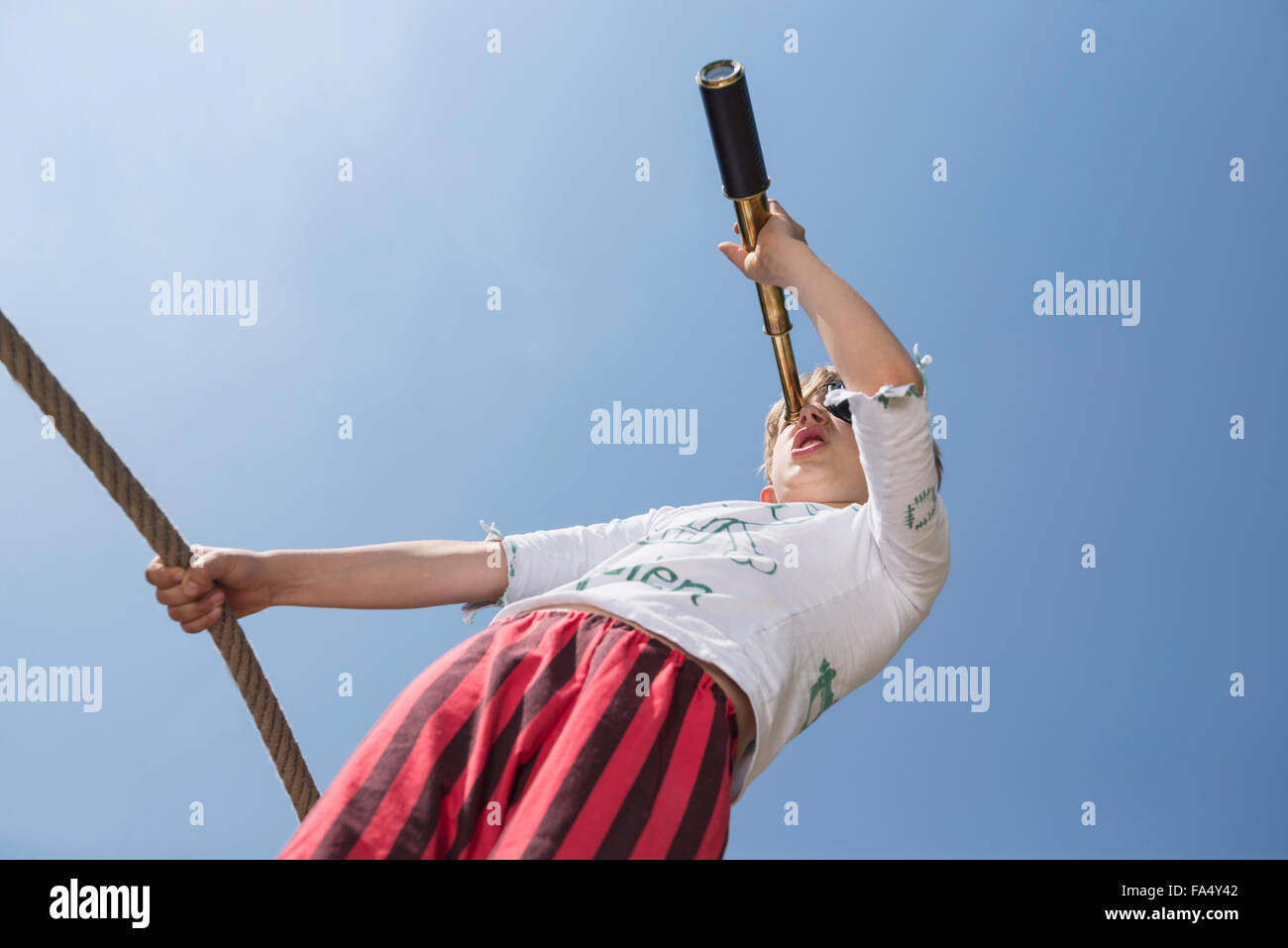 Boy standing on pirate ship in playground and looking through telescope, Bavaria, Germany - Stock Image