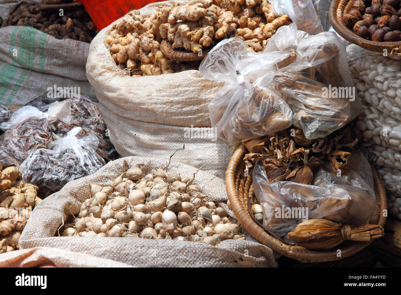 Bags of cooking spices and aromatics in an African market.  Seens are ginger, garlic, nuts, onions. - Stock Image