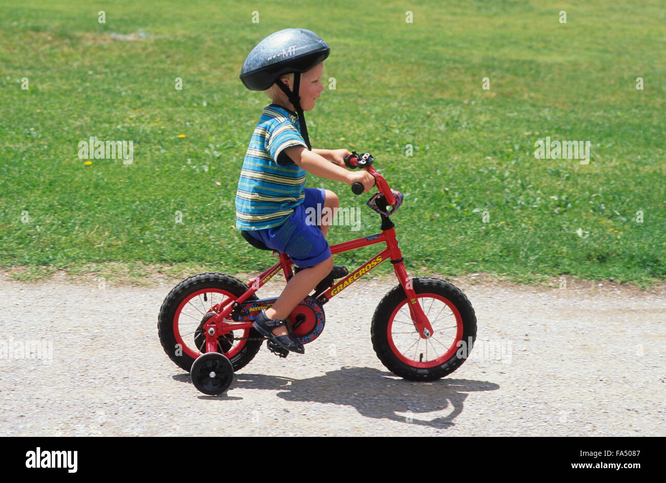 Cycling Young Boy On Bike With Helmet And Stabilisers Boy About 2