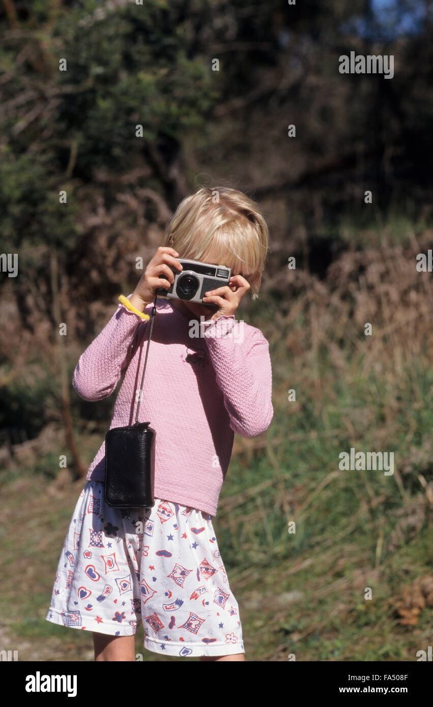 Young girl about 7 taking a photograph using an old film camera. - Stock Image