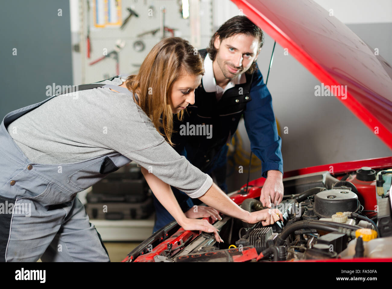 Auto mechanic guiding a female trainee in garage - Stock Image