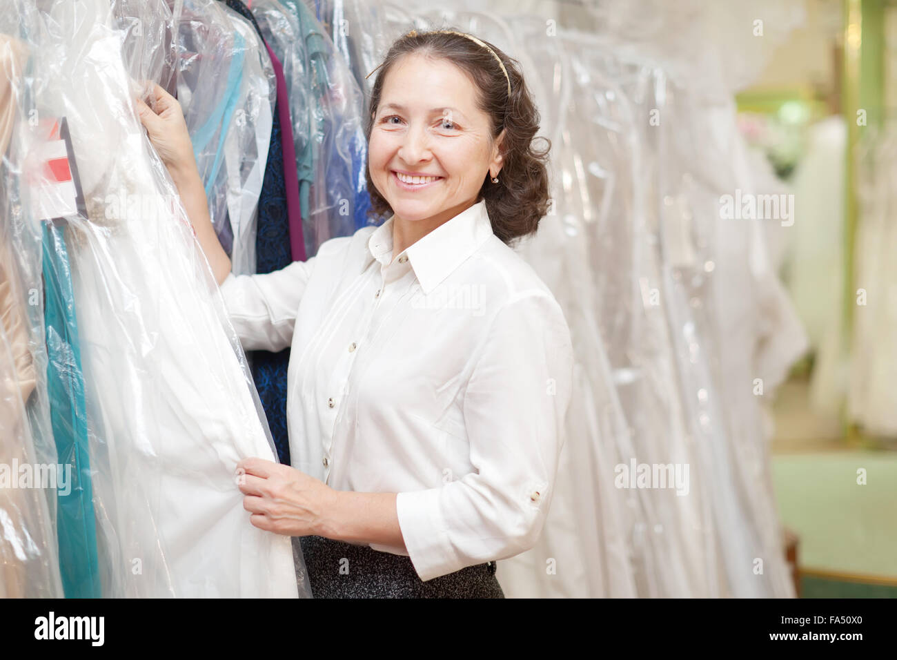 Smiling mature woman looking evening dress at boutique Stock Photo ...