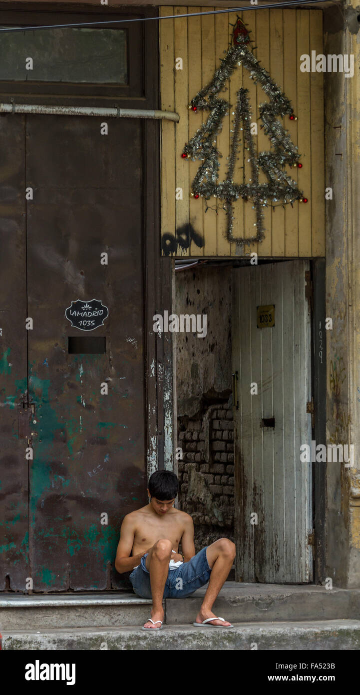 Downtown La Boca, Buenos Aires, Argentina.  A boy sits on a step under a Christmas decoration - Stock Image