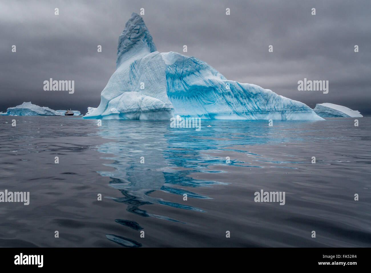Huge iceberg with a cruise ship for size comparison, set off vibrantly against the moody sky, Antarctica - Stock Image