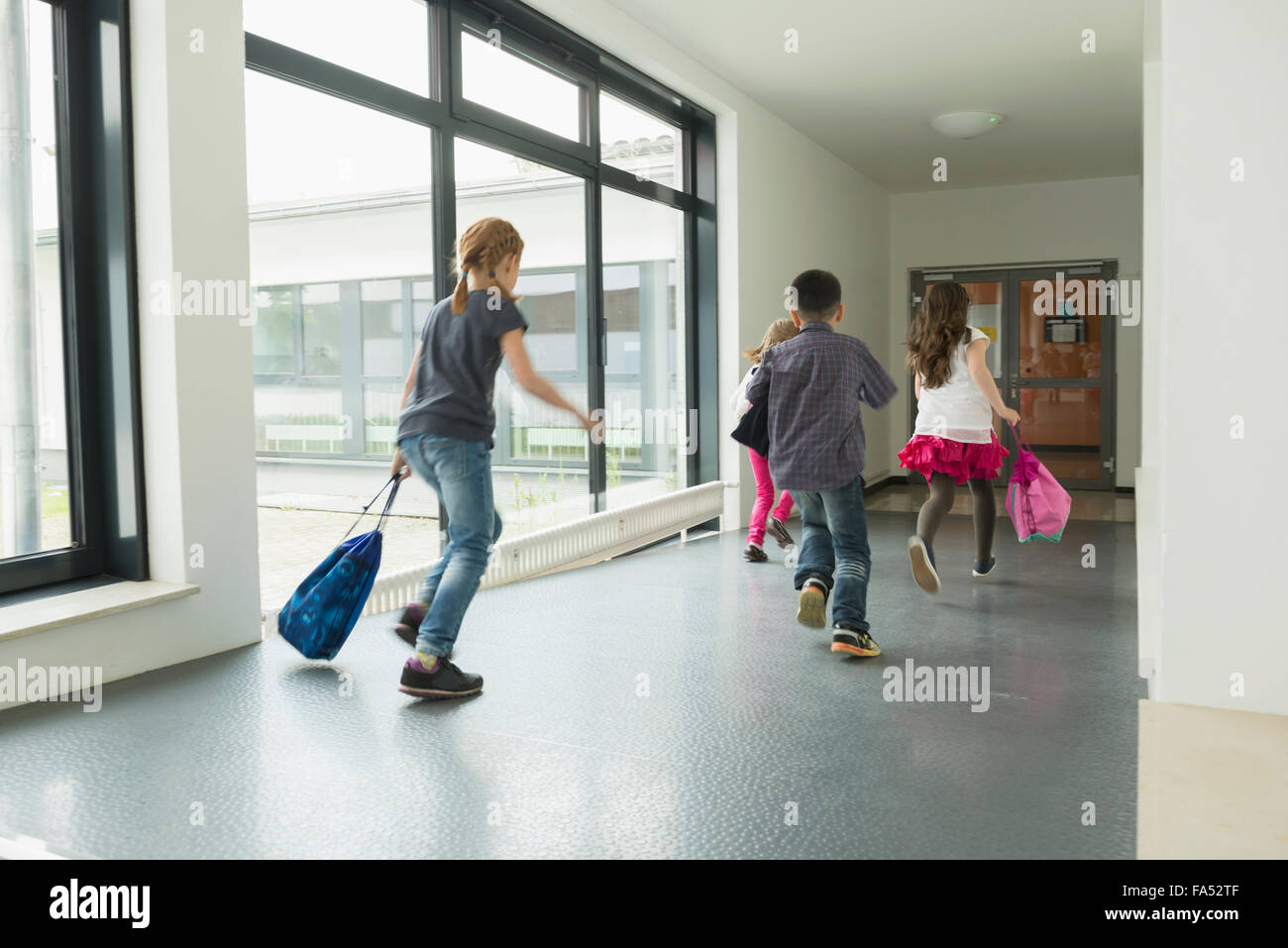 Children running with sports bags in corridor of sports hall, Munich, Bavaria, Germany - Stock Image