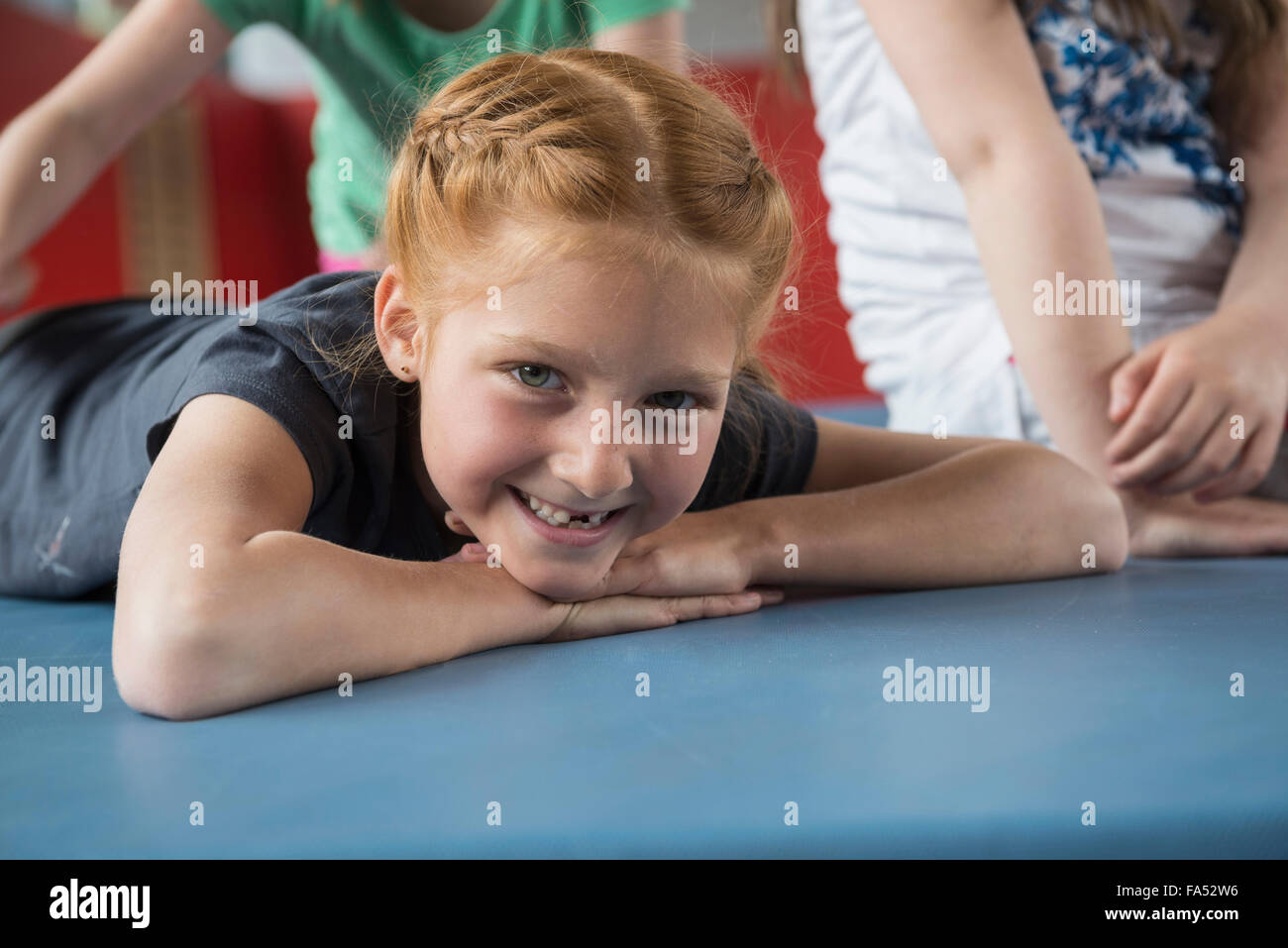 Girl lying on exercise mat in large gym of school, Bavaria, Munich, Germany - Stock Image