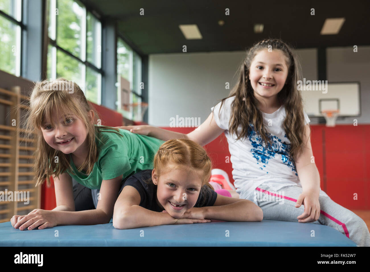 Girls resting on exercise mat in sports hall, Bavaria, Munich, Germany Stock Photo