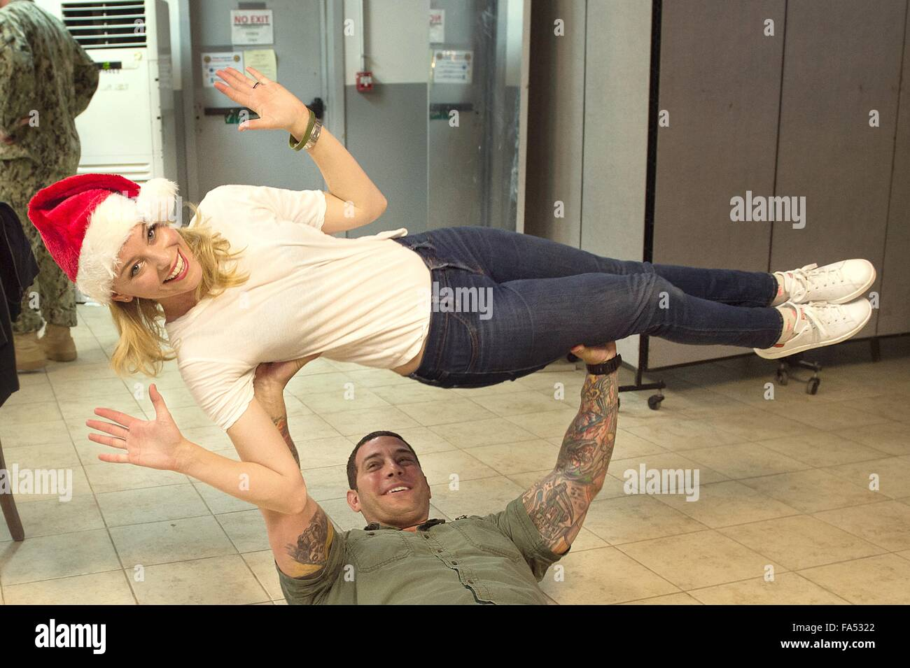 Actress Elizabeth Banks is lifted by a U.S. Marine during a visit with soldiers for the annual USO Christmas show Stock Photo