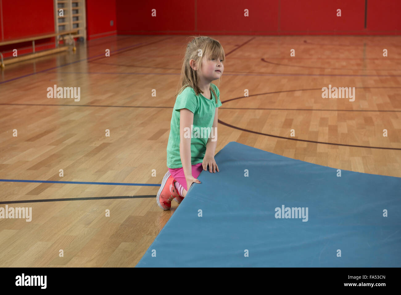 Girl trying to lift up heavy exercise mat in basketball court of sports hall, Munich, Bavaria, Germany - Stock Image