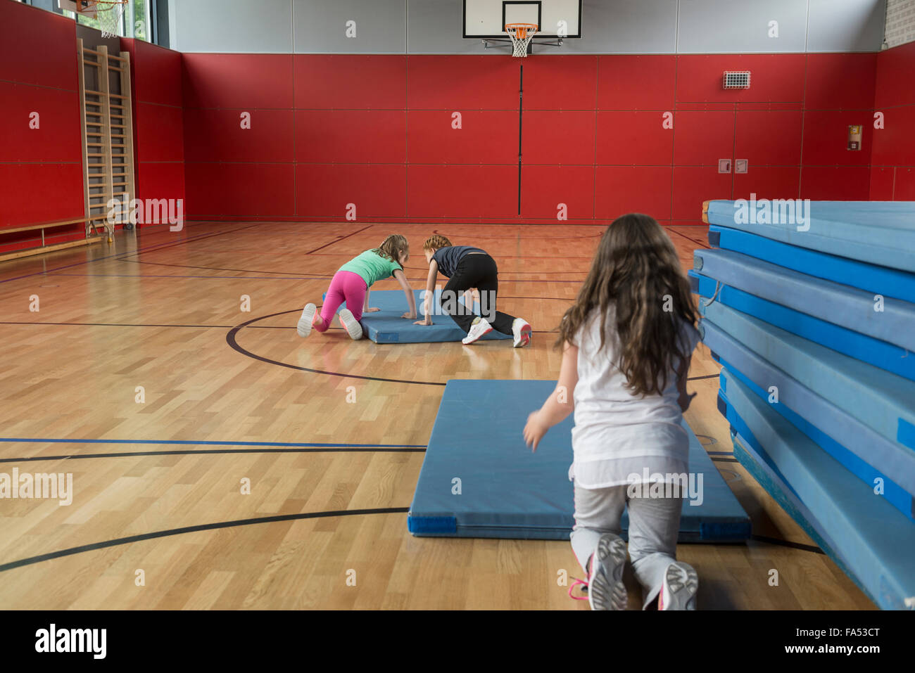 Girls arranging the sports mats in basketball court, Munich, Bavaria, Germany - Stock Image