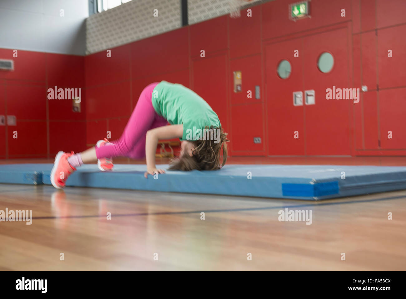 Girl doing somersault on exercise mat in sports hall, Munich, Bavaria, Germany - Stock Image