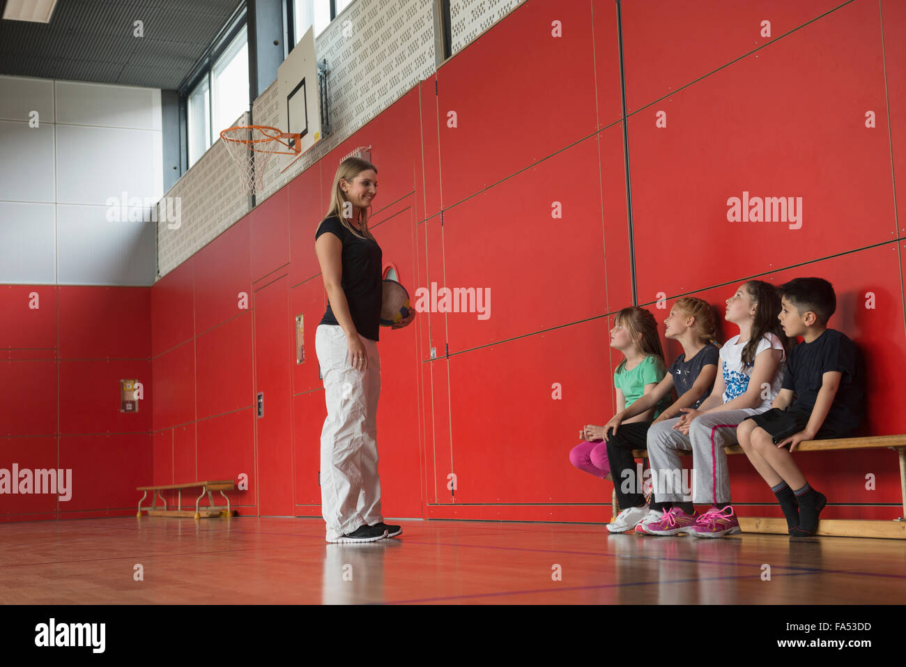 Teacher giving advice for group game to children in sports hall, Munich, Germany, Bavaria Stock Photo