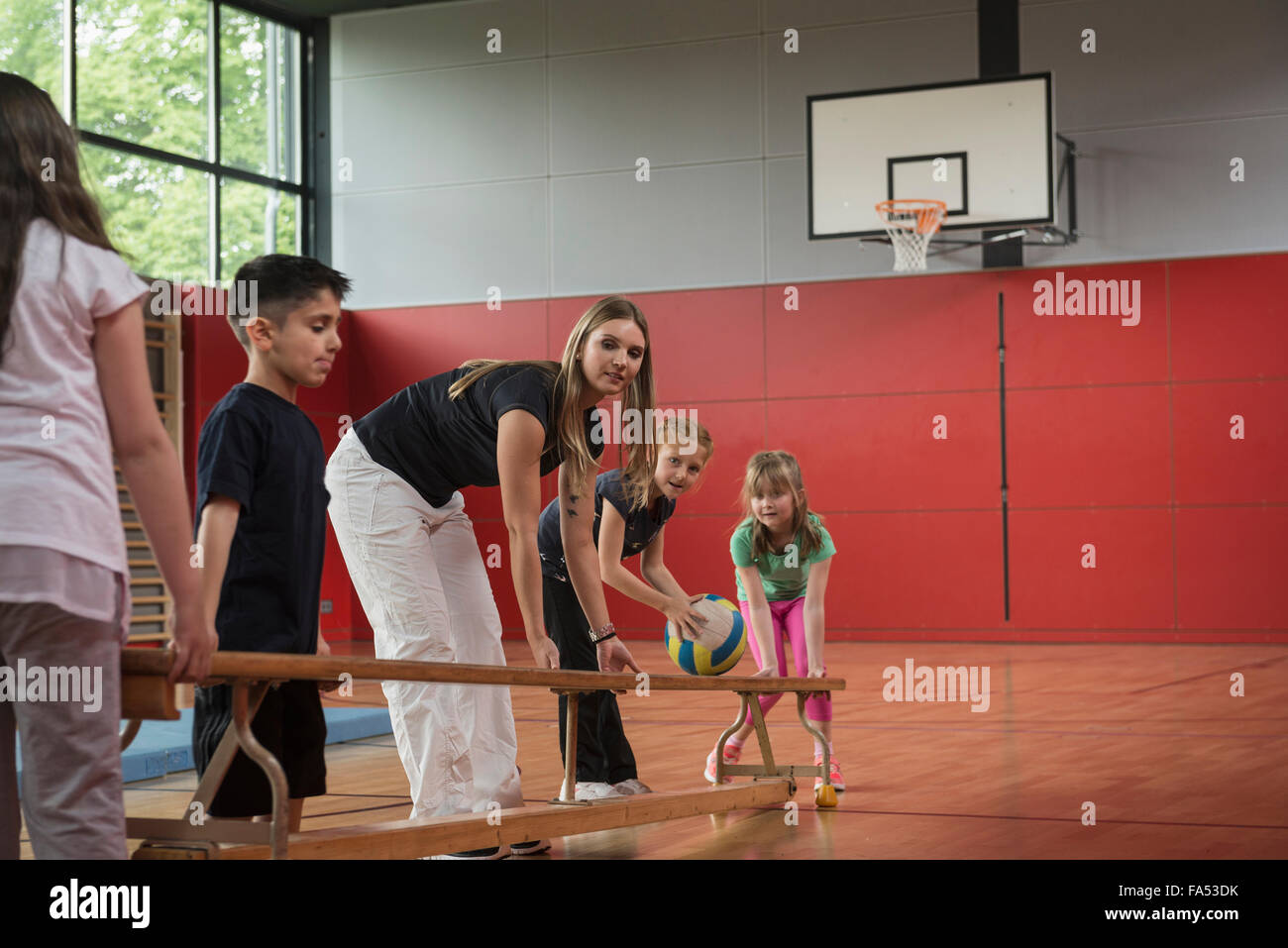 Teacher and students carrying bench in sports hall, Munich, Bavaria, Germany - Stock Image