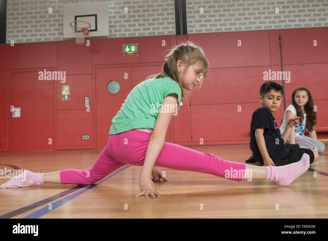 Girl amazed others by splitting her legs in sports hall, Munich, Bavaria, Germany - Stock Image