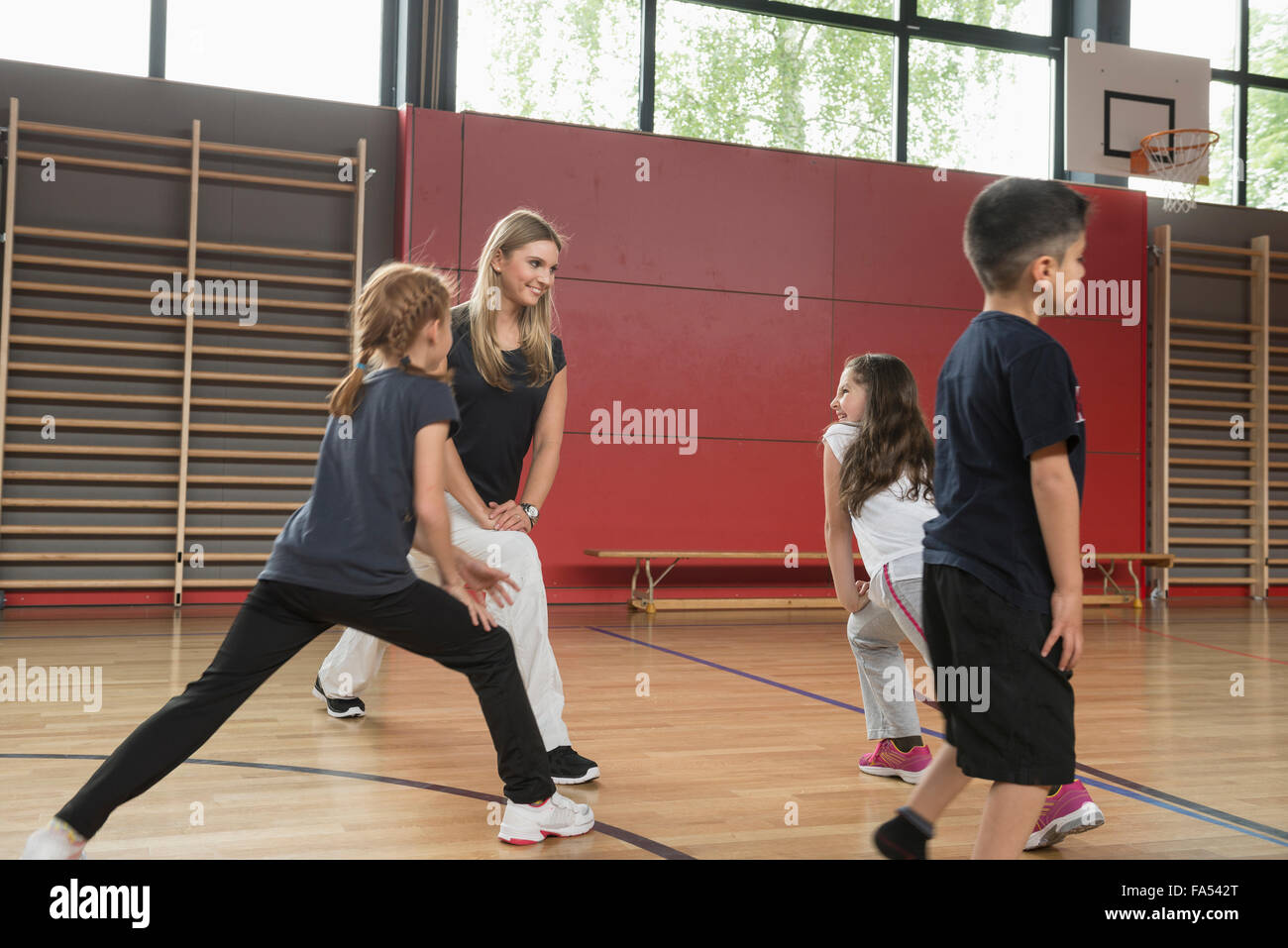 Teacher doing extension exercise with school children in sports hall, Munich, Bavaria, Germany - Stock Image