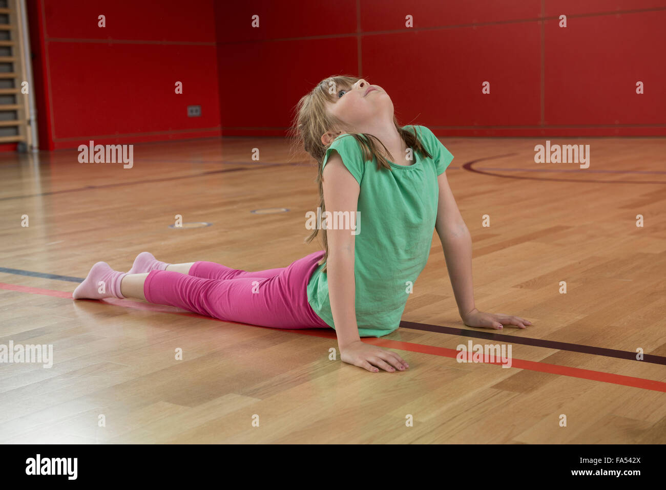 Girl practicing upward facing dog position in sports hall, Munich, Bavaria, Germany - Stock Image