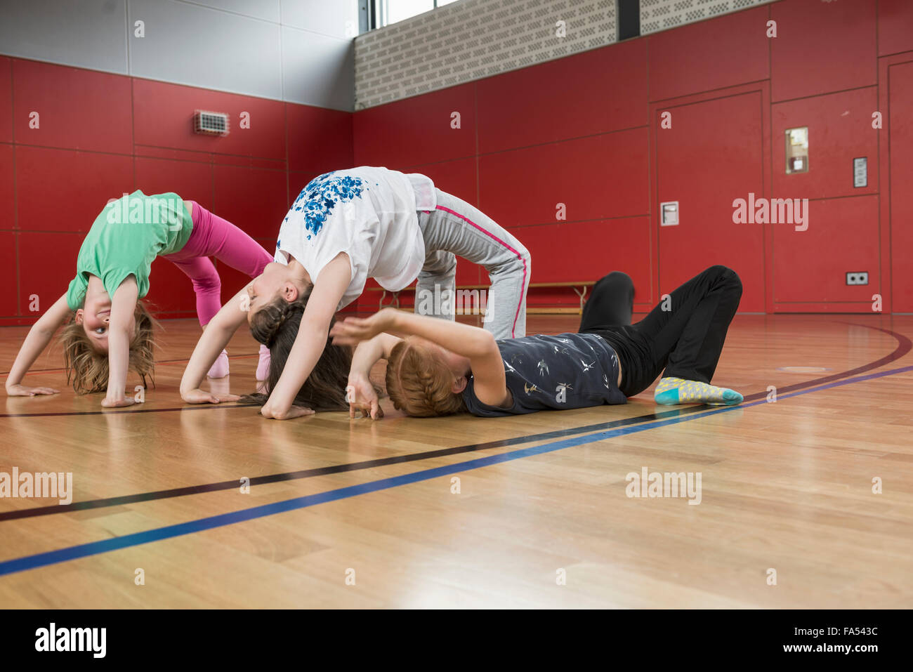 Girls doing bridge position yoga in sports hall, Munich, Bavaria, Germany - Stock Image