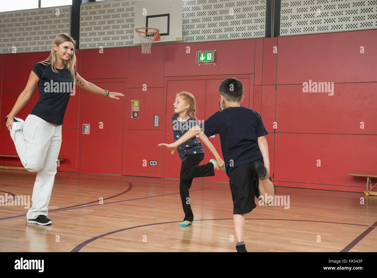 Teacher with children doing exercise in sports hall, Munich, Bavaria, Germany - Stock Image