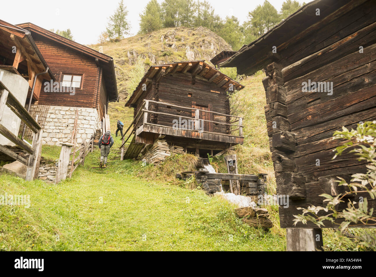 Rear view of two mature hikers passing by cottages, Austrian alps, Carinthia, Austria - Stock Image