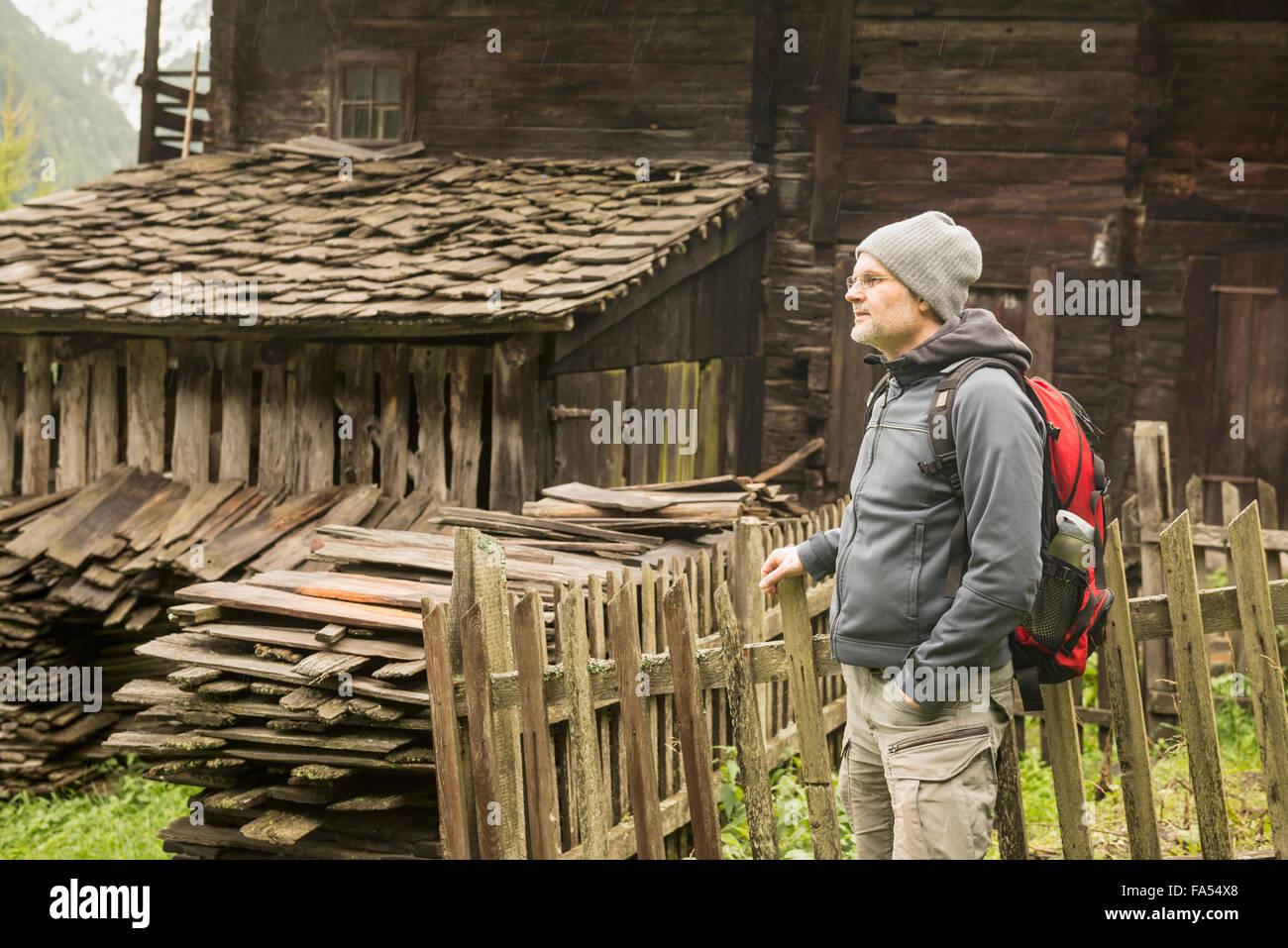 Mature hiker standing near cottage at rainy day, Austrian alps, Carinthia, Austria - Stock Image