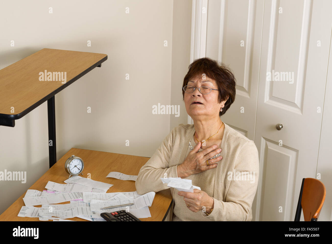 Senior woman feeling ill with her financial bills. In debt concept. - Stock Image