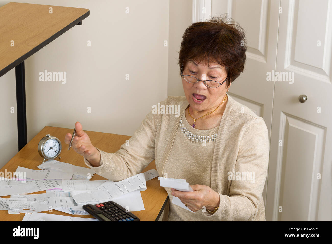 Senior woman in shock of her financial bills. In debt concept. - Stock Image