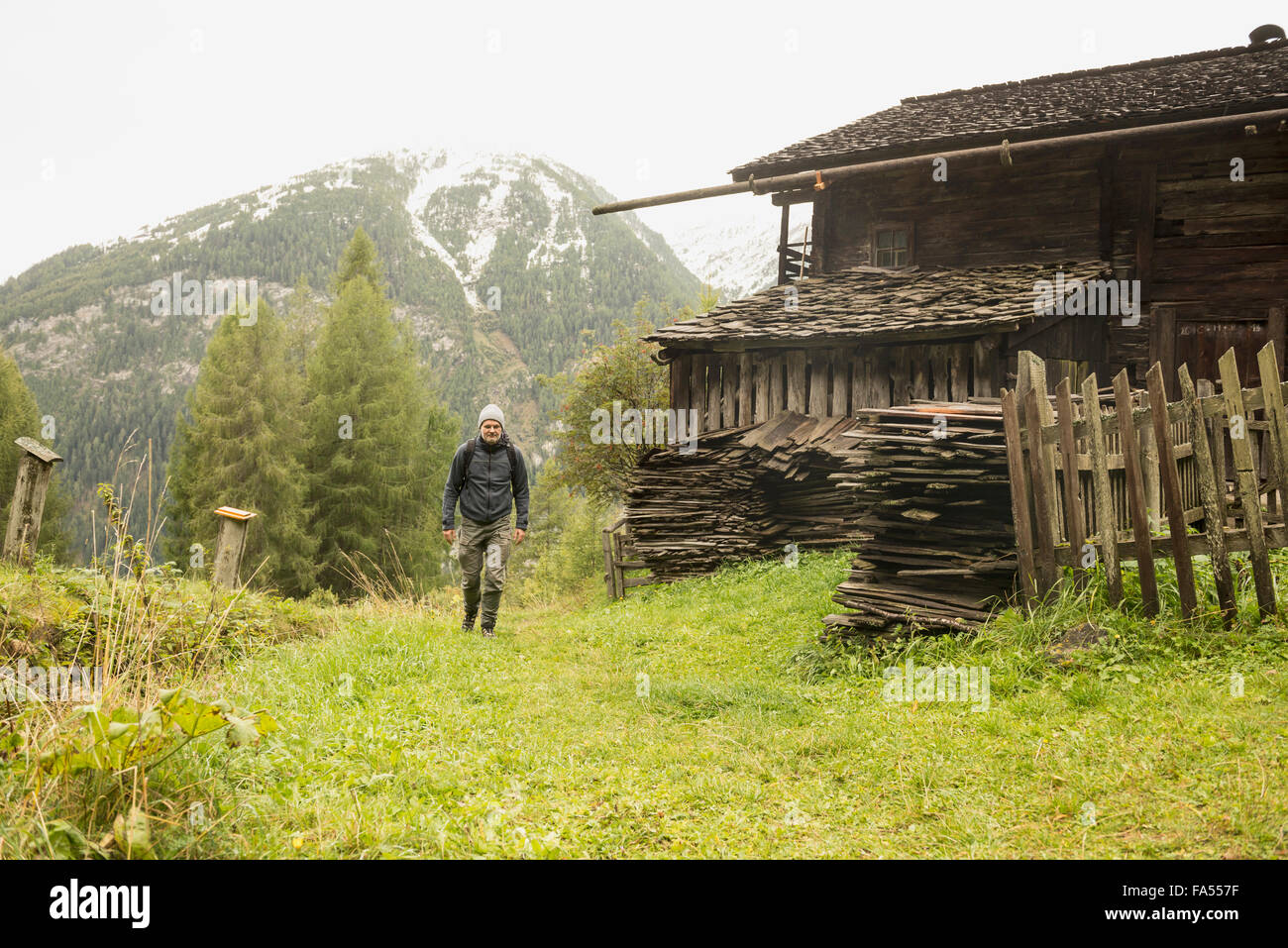 Mature hiker passing by cottage at rainy day, Austrian alps, Carinthia, Austria - Stock Image