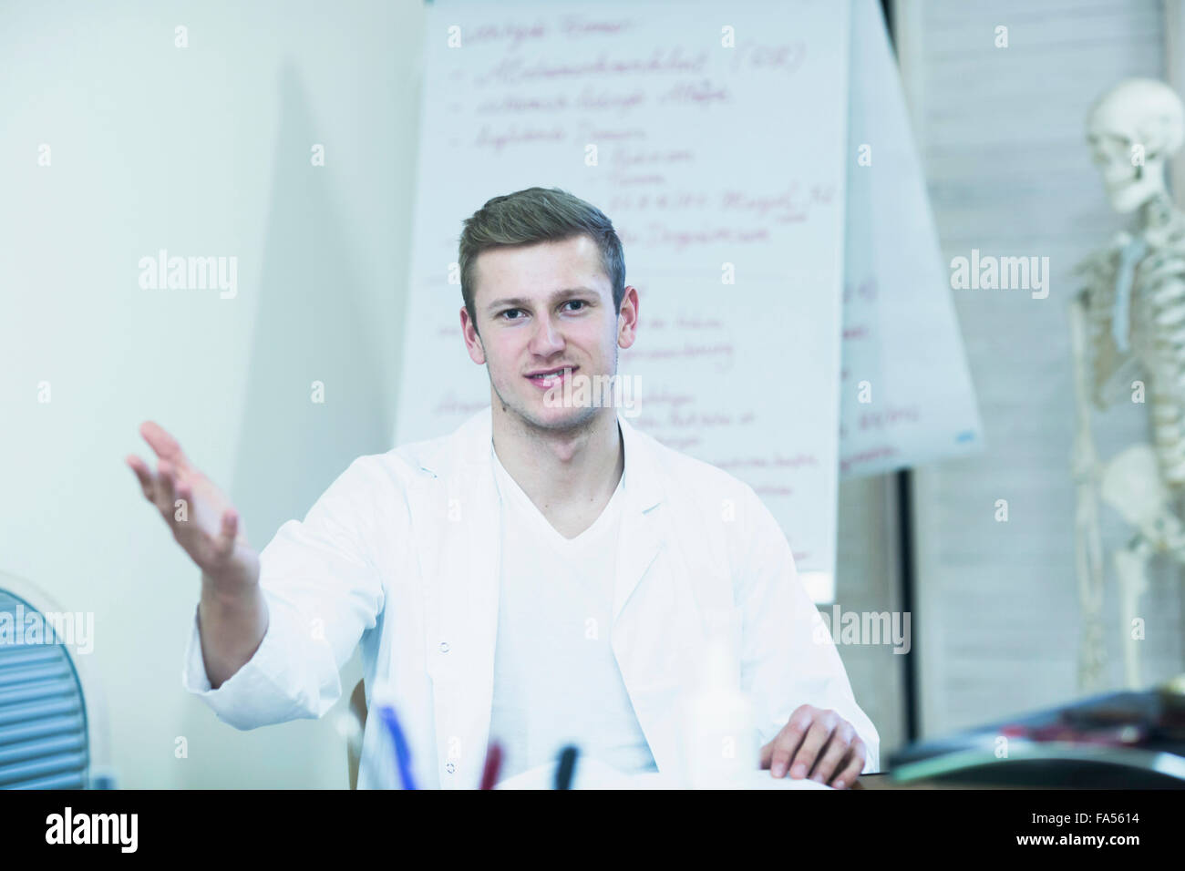 Portrait of a young doctor explaining about skeleton in his office, Freiburg Im Breisgau, Baden-Württemberg, - Stock Image