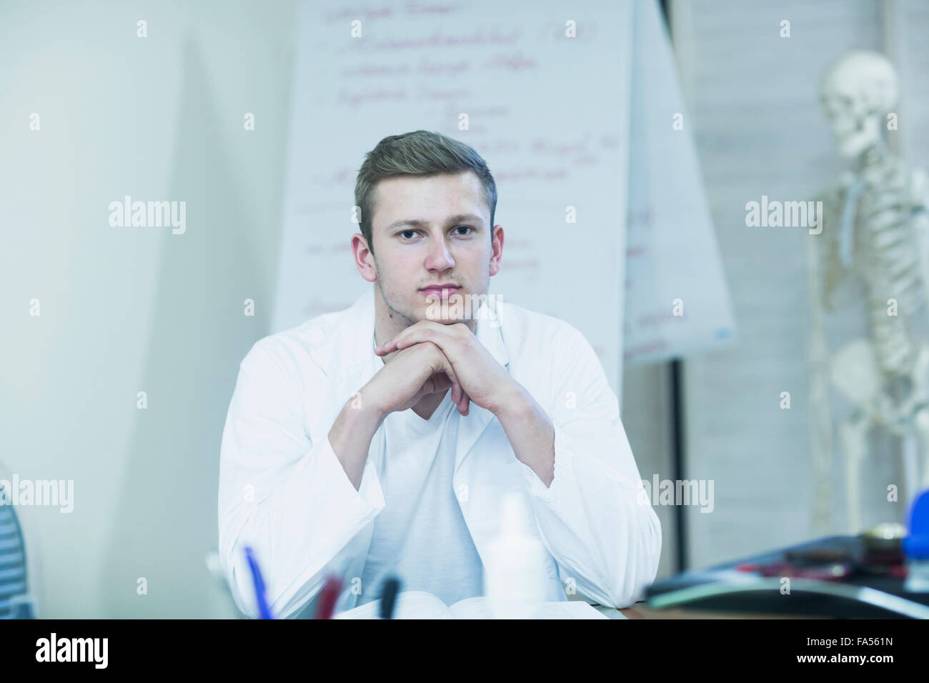 Portrait of a young doctor sitting in his office and skeleton in the background, Baden-Württemberg, Germany - Stock Image