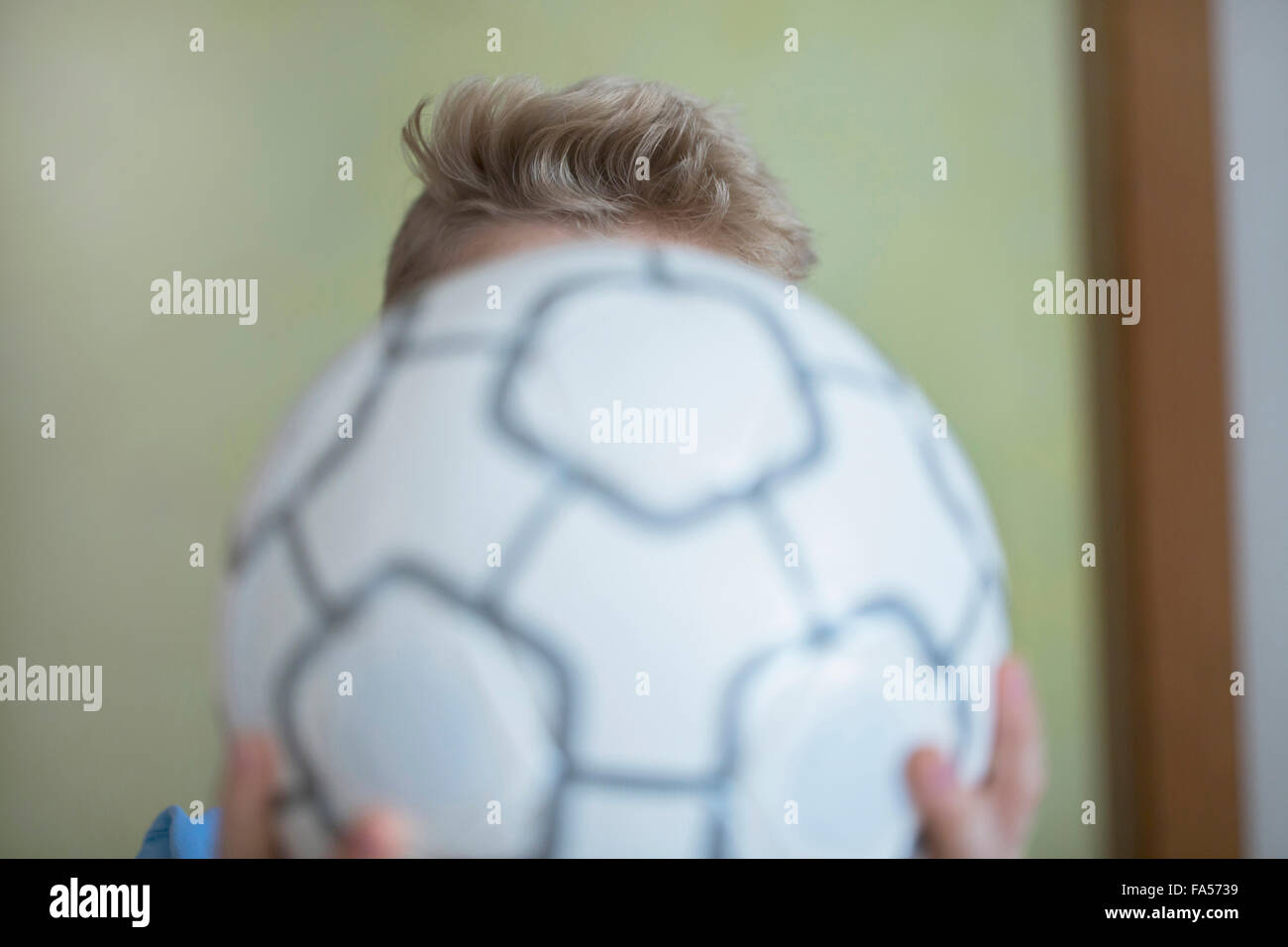 Boy holding football in front of his face, Freiburg im Breisgau, Baden-Württemberg, Germany - Stock Image
