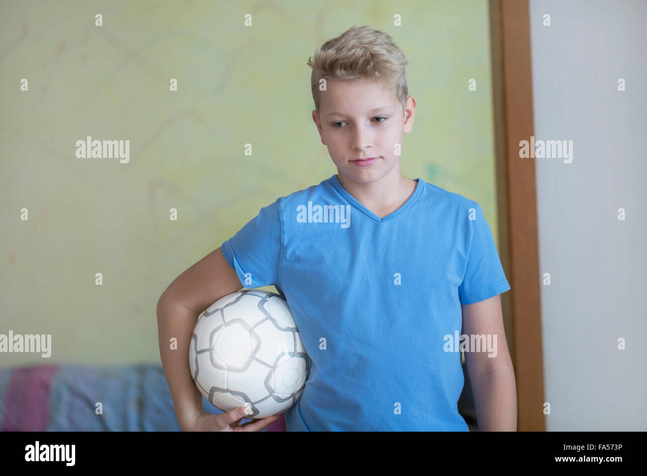 Boy holding football under his arm and looking down, Freiburg im Breisgau, Baden-Württemberg, Germany - Stock Image